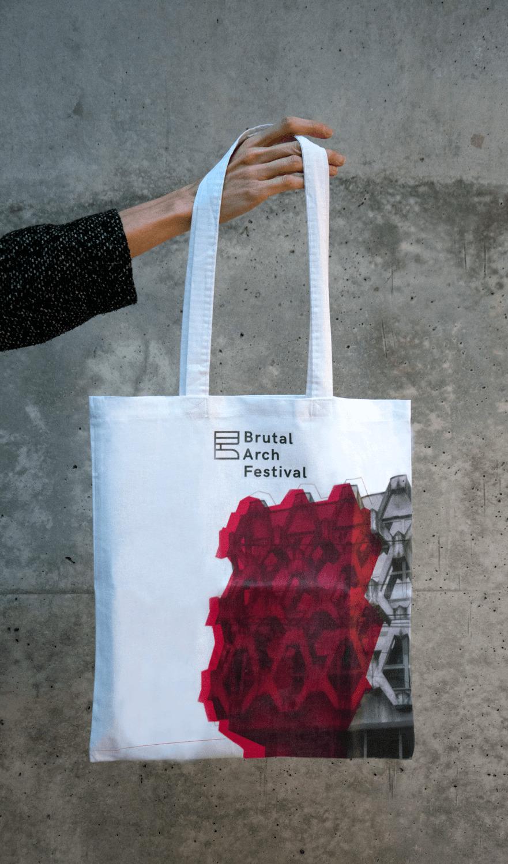 ręka trzyma torbę z materiału z napisem Brutal Arch Festival